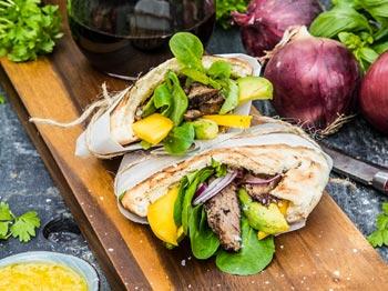 Flankstek i pitabröd med kikärtsdressing, grillad mango och avocadosallad
